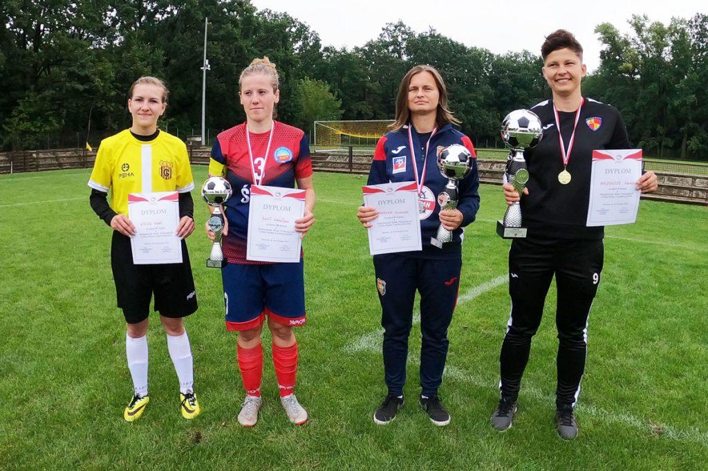 Zdjecie 4 piłkarek z dyplomami i pucharami w rękach. Mistrzostwa Polski Niesłyszących w Piłce Nożnej 7-osobowej Kobiet w Warszawie