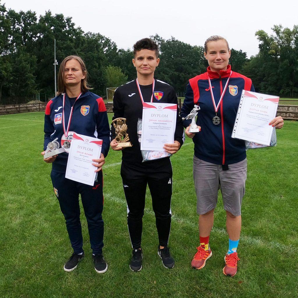 zdjcie trzech kobiet, kapitanów drużyn, tyrzymających w rękach puchary i dyplomy z Mistrzostw Polski Niesłyszących w Piłce Nożnej 7-osobowej Kobiet w Warszawie