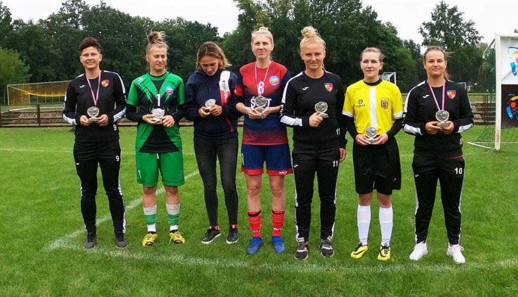 Zdjęcie siedmiu piłkarek z medalami i pucharami w ręku.