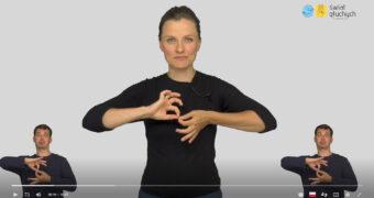 zrzut ekranu z odtwarzacza. Po środku lektor wykonuje znak, symbol ikonki języka migowego. Po lewej i po prawej stronie, na dole, tłumacz języka migowego wykonuje ten sam znak.