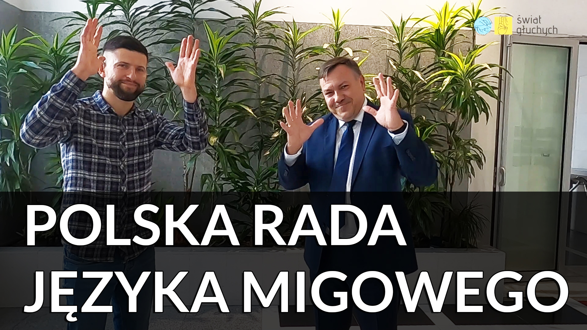 Zdjęcie swóch usmiechniętych mężczyzn machajacych do kamery. Po lewej Maciej Joniuk (Świat Głuchych), po prawej Adam Stromidło (PZG Oddział Małopolski). Poniżej podpisL Polska Rada Języka Migowego.